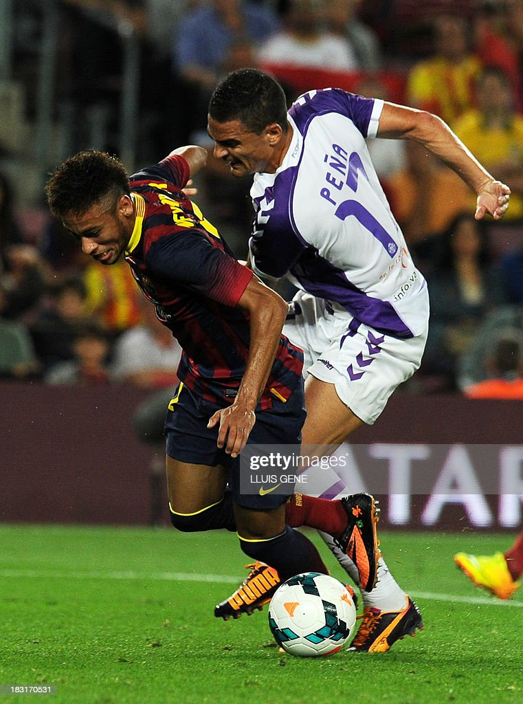 Barcelona's Brazilian forward Neymar da Silva Santos (L) vies with Valladolid's defender Carlos Pena (R) during the Spanish league football match FC Barcelona vs Real Valladolid CF at the Camp Nou stadium in Barcelona on October 5, 2013.