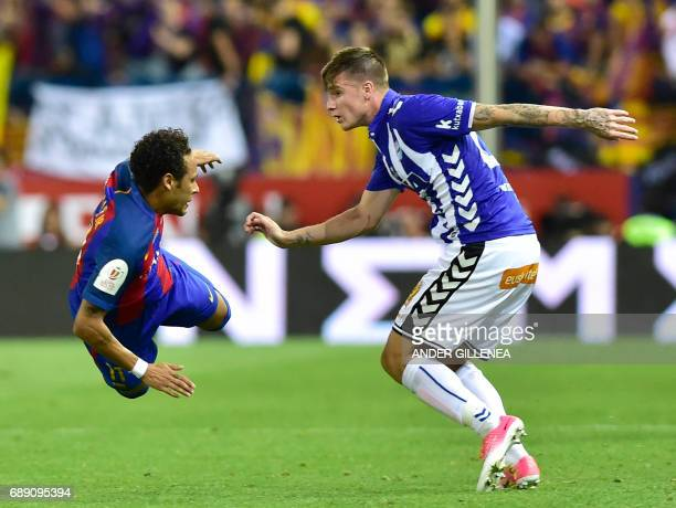 Barcelona's Brazilian forward Neymar falls in front of Deportivo Alaves' defender Carlos Vigaray during the Spanish Copa del Rey final football match...