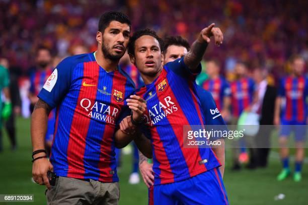 Barcelona's Brazilian forward Neymar gestures past Barcelona's Uruguayan forward Luis Suarez at the end of the Spanish Copa del Rey final football...