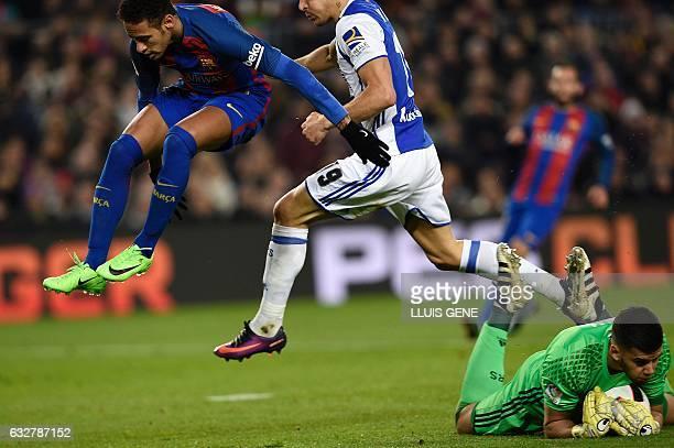 Barcelona's Brazilian forward Neymar jumps past Real Sociedad's Argentinian goalkeeper Geronimo Rulli and Real Sociedad's defender Yuri Berchiche...