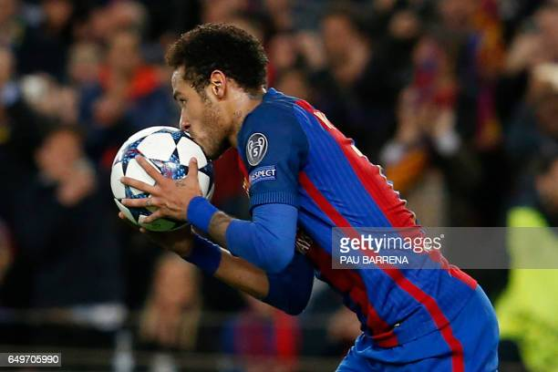 TOPSHOT Barcelona's Brazilian forward Neymar kisses the ball as he celebrates after scoring during the UEFA Champions League round of 16 second leg...