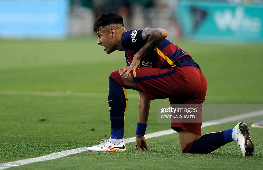 Barcelona's Brazilian forward Neymar kneels on the pitch during the Spanish league football match Real Betis Balompie vs FC Barcelona at the Benito Villamarin stadium in Sevilla on April 30, 2016. / AFP / CRISTINA
