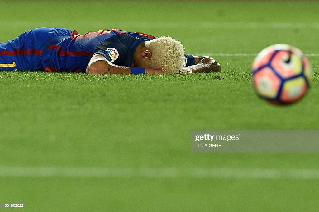 Barcelona's Brazilian forward Neymar lies on the pitch after missing a goal during the Spanish league football match FC Barcelona vs Deportivo Alaves at the Camp Nou stadium in Barcelona on September 10, 2016. / AFP / LLUIS