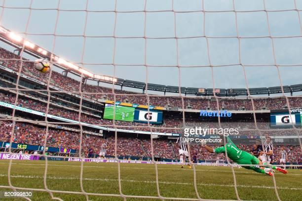 Barcelona's Brazilian forward Neymar scores past Juventus' goalkeeper from Italy Gianluigi Buffon during the International Champions Cup match...