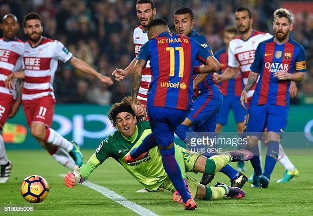 Barcelona's Brazilian forward Neymar shoots in front of Granada's goalkeeper Guillermo Ochoa during the Spanish league football match between FC...
