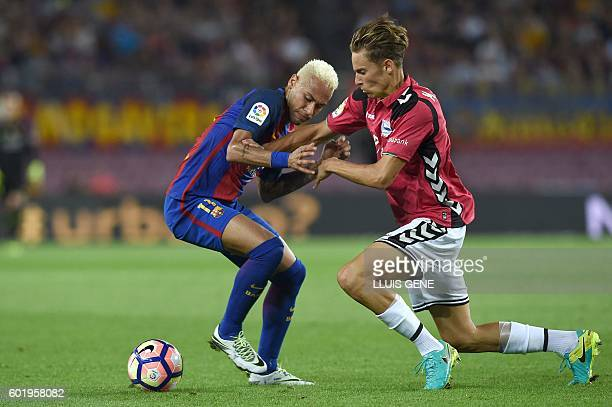 Barcelona's Brazilian forward Neymar vies with Alaves' defender Raul Garcia during the Spanish league football match FC Barcelona vs Deportivo Alaves...