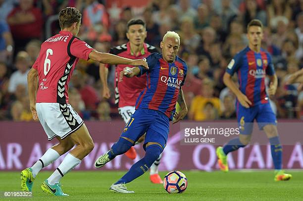 Barcelona's Brazilian forward Neymar vies with Alaves' midfielder Marcos Llorente during the Spanish league football match FC Barcelona vs Deportivo...