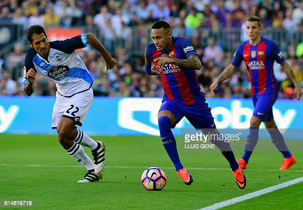 Barcelona's Brazilian forward Neymar vies with Deportivo's Costa Rican midfielder Celso Borges Mora during the Spanish league football match FC...