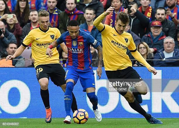 Barcelona's Brazilian forward Neymar vies with Malaga's defender Diego Llorente and Malaga's midfielder Ontiveros during the Spanish league football...