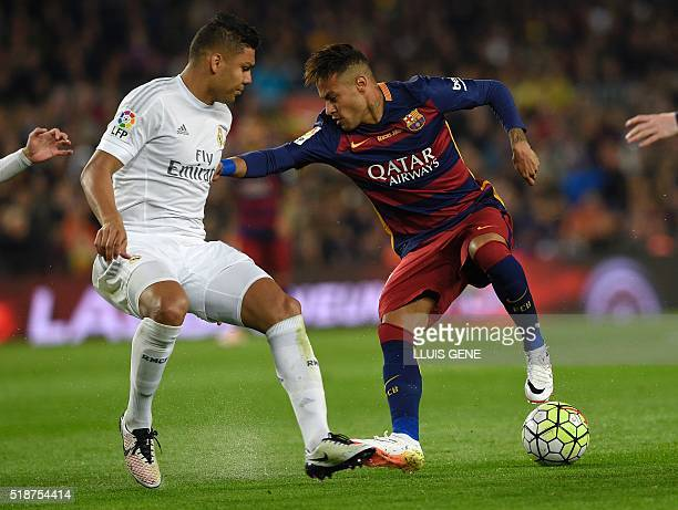 Barcelona's Brazilian forward Neymar vies with Real Madrid's Brazilian midfielder Casemiro during the Spanish league 'Clasico' football match FC...