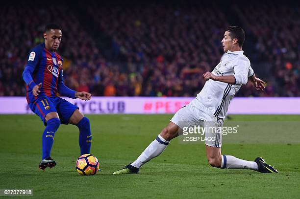 Barcelona's Brazilian forward Neymar vies with Real Madrid's Portuguese forward Cristiano Ronaldo during the Spanish league football match FC...