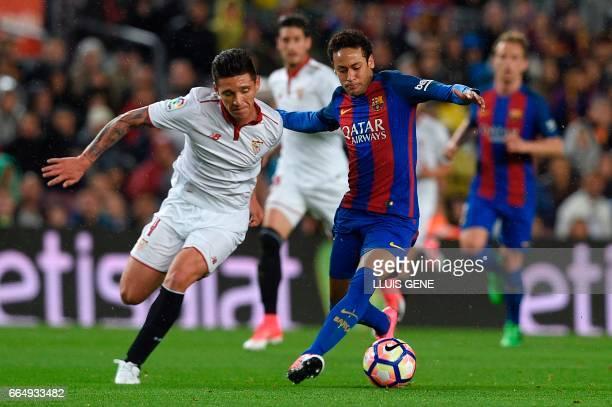Barcelona's Brazilian forward Neymar vies with Sevilla's Argentinian midfielder Matias Kranevitter during the Spanish league football match FC...