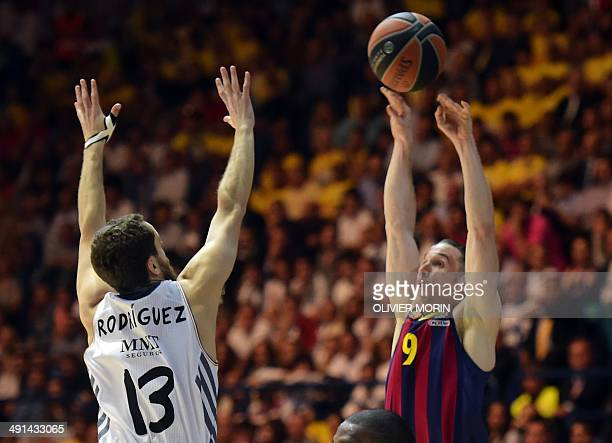 Barcelona's Brazilian guard Marcelo Huertas tries to score past Real Madrid's guard Sergio Rodriguez during their Euroleague 2014 semifinal Four...