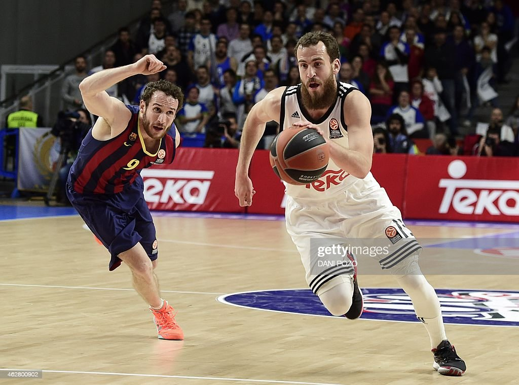 Barcelona's Brazilian guard Marcelo Huertas vies with Real Madrid's guard Sergio Rodriguez during the Euroleague basketball Top 16 round 6 match Real...