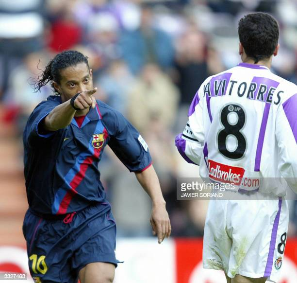 Barcelona's Brazilian Ronaldinho celebrates after scoring their second goal for his team in front of Valladolid's Javi Torres during their Spanish...