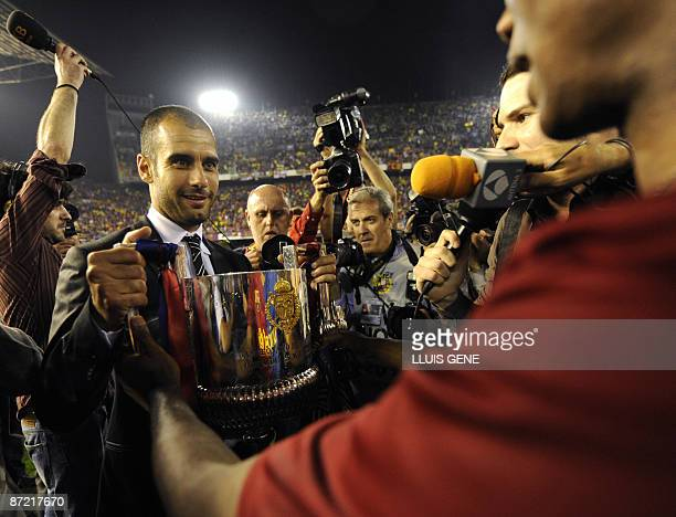 Barcelona´s Cameroonian forward Samuel Eto´o gives the trophy to Barcelona´s coach Pep Guardiola after winning the Spanish King´s Cup final match...