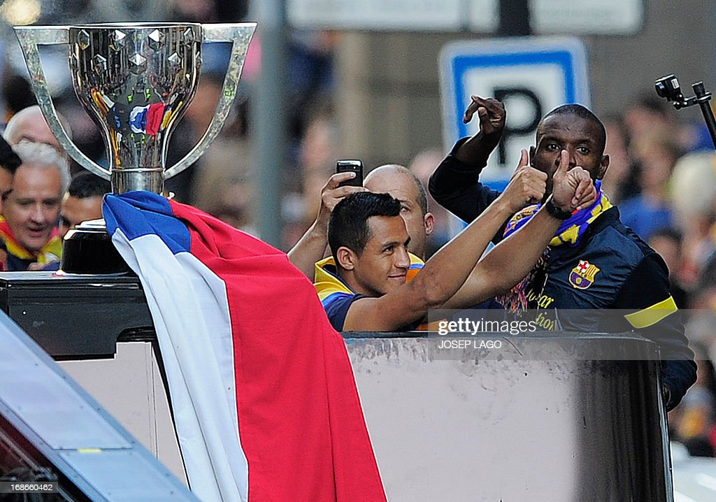 Barcelona's Chilean forward Alexis Sanchez (2ndR) and Barcelona's French defender Eric Abidal (R) gestures as they parade on a bus through a crowd of supporters as they celebrate in the streets of Barcelona on May 13, 2013, two days after their team won the Spanish league. The Catalans didn't even need to set foot on the pitch to seal the title on May 11 as Real Madrid's 1-1 draw with Espanyol meant Barca had already been crowned champions before their 2-1 win over Atletico Madrid on May 12, 2013.