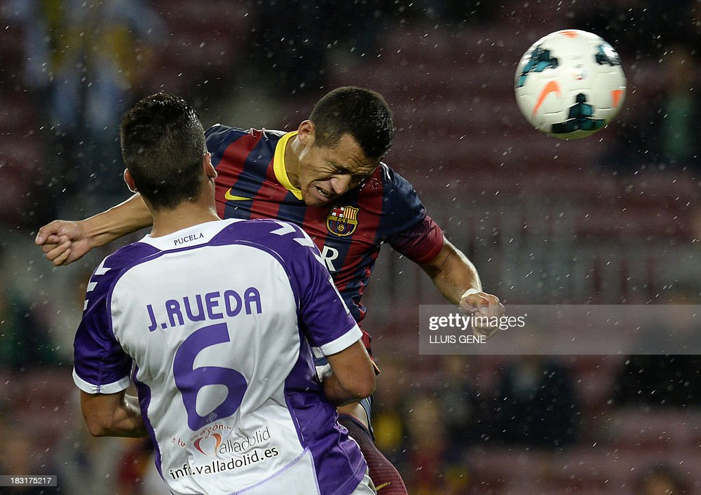Barcelona's Chilean forward Alexis Sanchez (top) heads the ball as he vies with Valladolid's defender Jesus Rueda during the Spanish league football match FC Barcelona vs Real Valladolid CF at the Camp Nou stadium in Barcelona on October 5, 2013.