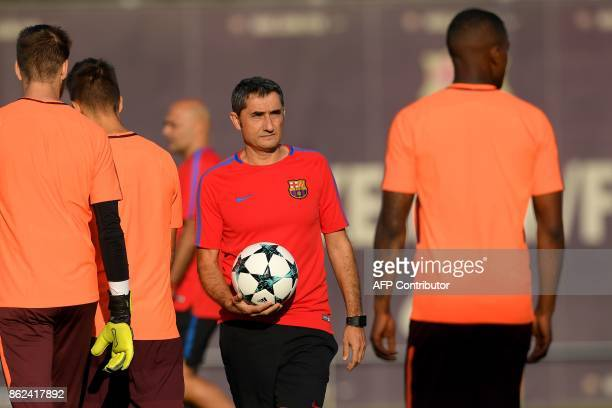 Barcelona's coach Ernesto Valverde holds a ball during a training session at the Joan Gamper Sports Center in Sant Joan Despi near Barcelona on...