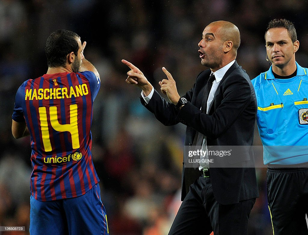 Barcelona's coach Josep Guardiola gives orders to Barcelona's Argentinian midfielder Javier Mascherano (L) during their Spanish League football match between FC Barcelona and Atletico de Madrid on September 24, 2011 at Camp Nou stadium in Barcelona.
