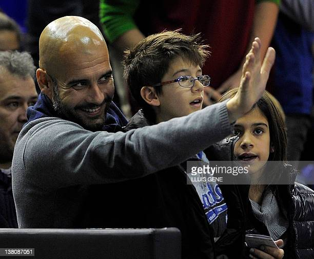 Barcelona's coach Josep Guardiola holds his son Marius and daughter Maria during the Euroleague basketball match between Regal FC Barcelona and...