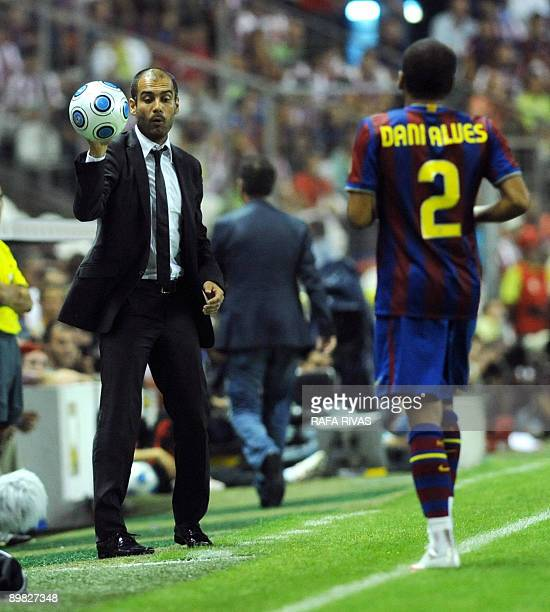 Barcelona's coach Pep Guardiola gives the ball to his player Dani Alves during their Spanish Supercup 1st leg football match against Athletic Bilbao...