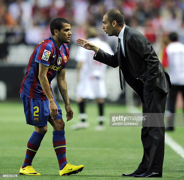 Barcelona's coach Pep Guardiola speaks with Barcelona's Brazilian defender Dani Alves during their Spanish league football match beetwen Sevilla and...