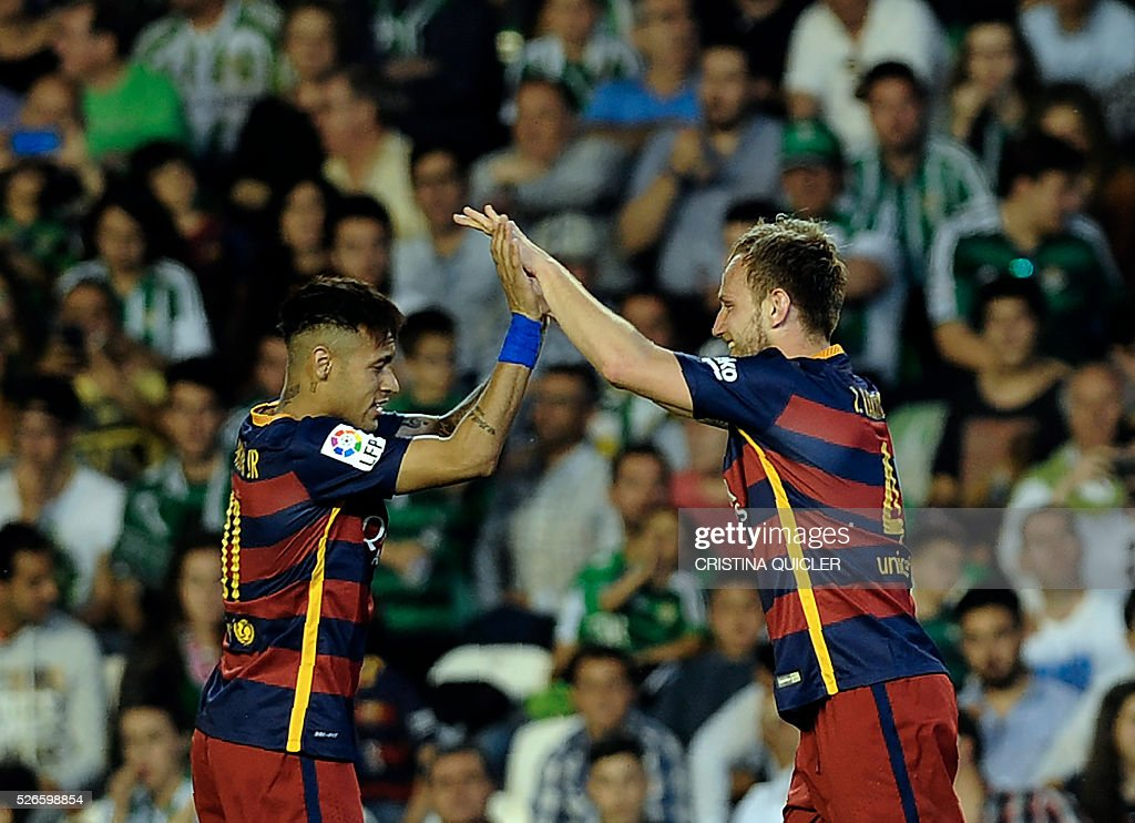 Barcelona's Croatian midfielder Ivan Rakitic (R) celebrates a goal with Barcelona's Brazilian forward Neymar (L) during the Spanish league football match Real Betis Balompie vs FC Barcelona at the Benito Villamarin stadium in Sevilla on April 30, 2016. / AFP / CRISTINA