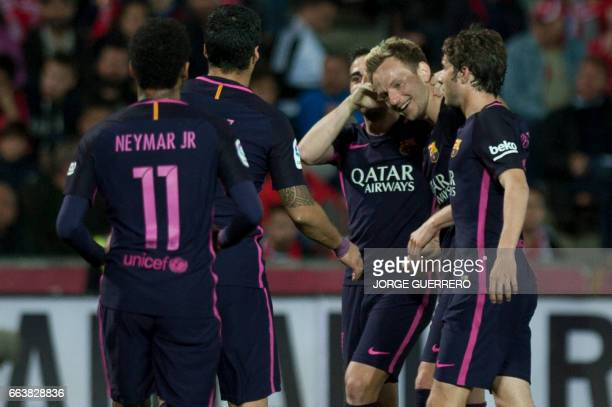 Barcelona's Croatian midfielder Ivan Rakitic celebrates a goal with teammates during the Spanish league football match Granada FC vs FC Barcelona at...