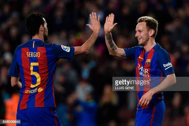 Barcelona's Croatian midfielder Ivan Rakitic celebrates with Barcelona's midfielder Sergio Busquets after scoring a goal during the Spanish league...