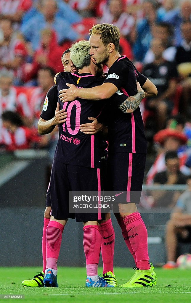 Barcelona's Croatian midfielder Ivan Rakitic is congratulated by teammates defender Jordi Alba and Argentinian forward Lionel Messi after scoring...