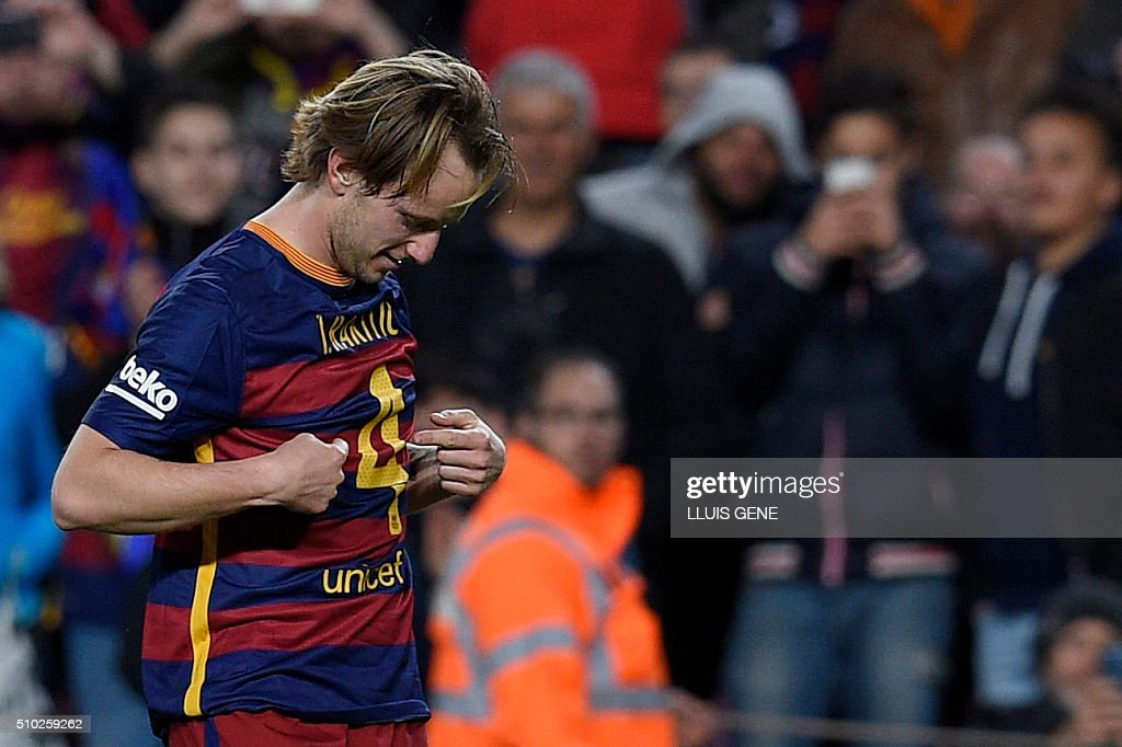 Barcelona's Croatian midfielder Ivan Rakitic points at his number as he celebrates a goal during the Spanish league football match FC Barcelona vs RC Celta de Vigo at the Camp Nou stadium in Barcelona on February 14, 2016. GENE
