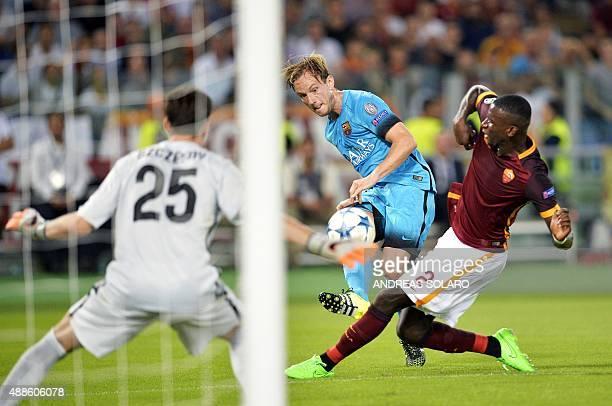 Barcelona's Croatian midfielder Ivan Rakitic tries to score next to Roma's German defender Antonio Rudiger during the UEFA Champions League football...