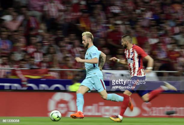 Barcelona's Croatian midfielder Ivan Rakitic vies with Atletico Madrid's Belgian midfielder Yannick FerreiraCarrasco during the Spanish league...