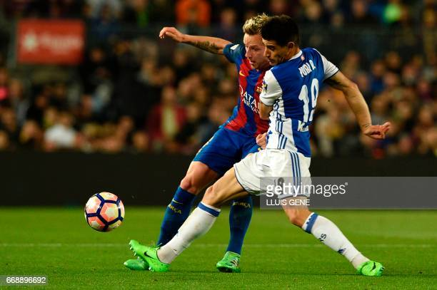Barcelona's Croatian midfielder Ivan Rakitic vies with Real Sociedad's defender Yuri Berchiche during the Spanish league football match FC Barcelona...