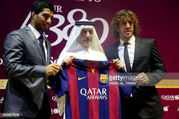 FC Barcelona's defender Carles Puyol forward Luis Suarez and Qatar Airways Chief Executive Officer Akbar alBaker pose for a picture during the...