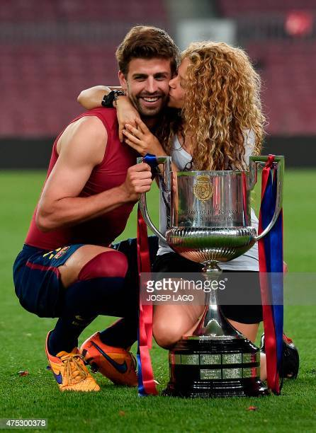 Barcelona's defender Gerard Pique and his wife Colombian singer Shakira pose with the trophy at the end of the Spanish Copa del Rey final football...