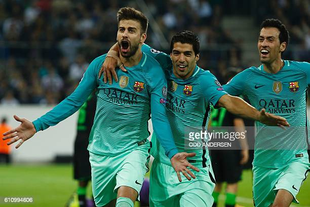 TOPSHOT Barcelona's defender Gerard Pique celebrates scoring the 12 goal with his teammates Uruguayan forward Luis Suarez and midfielder Sergio...
