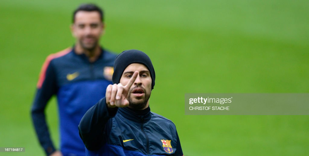 Barcelona's defender Gerard Pique (R) gestures in front of his teammate midfielder Xavi Hernandez during the final team training on the eve of the UEFA Champions League semi final first leg football match between FC Bayern Munich and FC Barcelona at the arena in Munich, southern Germany, on April 22, 2013. The semi final match will take place on April 23, 2013. AFP PHOTO/CHRISTOF STACHE