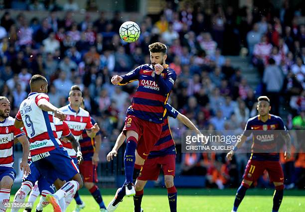 Barcelona's defender Gerard Pique heads the ball during the Spanish league football match Granada CF vs FC Barcelona at Nuevo Los Carmenes stadium in...