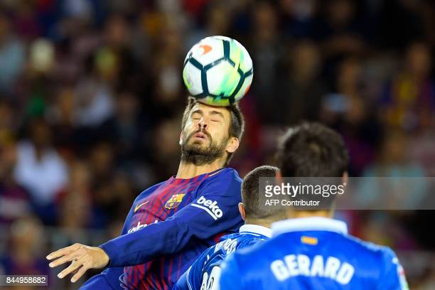 Barcelona's defender Gerard Pique heads the ball during the Spanish Liga football match Barcelona vs Espanyol at the Camp Nou stadium in Barcelona on...