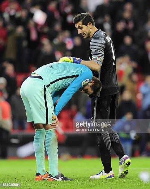 Barcelona's defender Gerard Pique is consoled by Athletic Bilbao's goalkeeper Gorka Iraizoz at the end of the Spanish Copa del Rey round of 16 first...