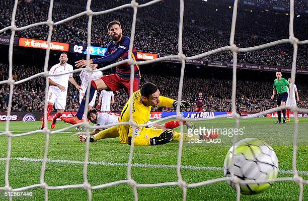 TOPSHOT Barcelona's defender Gerard Pique scores a goal next to Sevilla's goalkeeper Sergio Rico during the Spanish league football match FC...