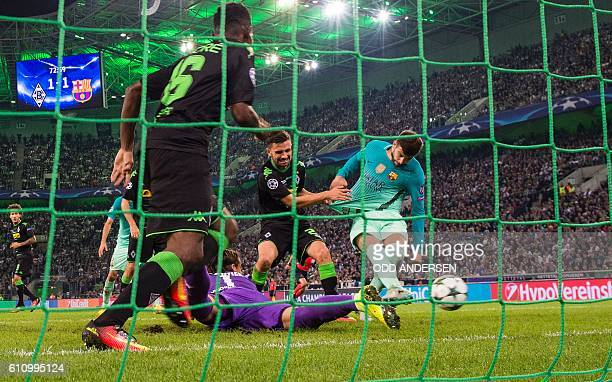 TOPSHOT Barcelona's defender Gerard Pique scores the 12 goal past Moenchengladbach's Swiss goalkeeper Yann Sommer during the UEFA Champions League...