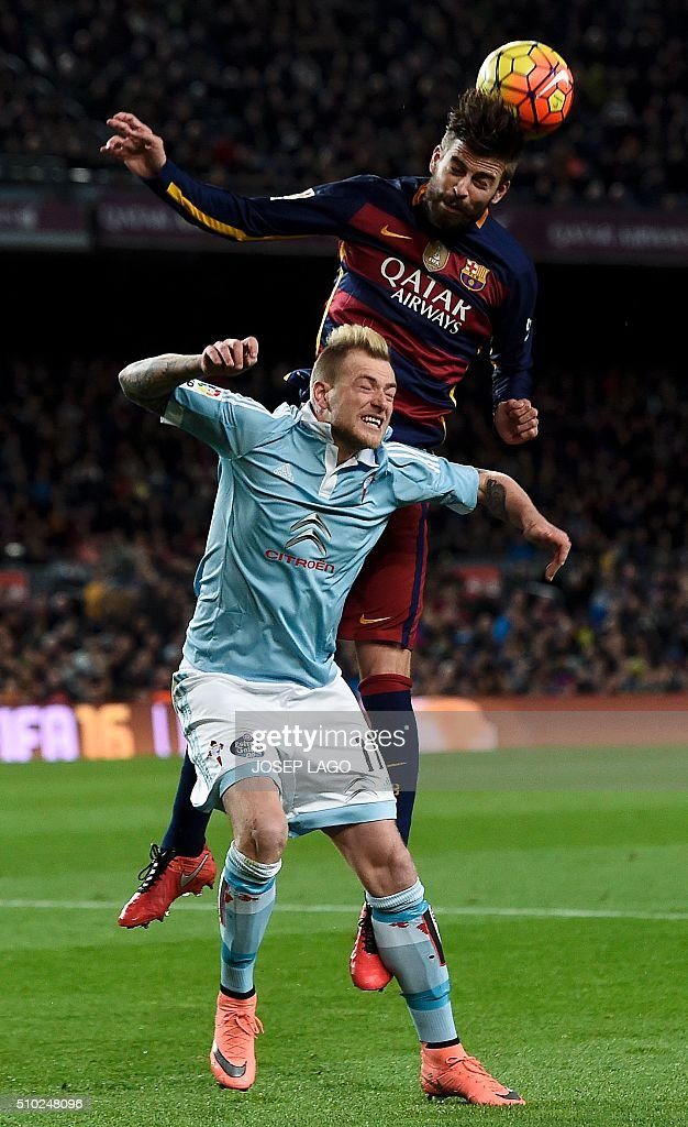 Barcelona's defender Gerard Pique (up) vies with Celta's Swedish forward John Guidetti during the Spanish league football match FC Barcelona vs RC Celta de Vigo at the Camp Nou stadium in Barcelona on February 14, 2016. LAGO