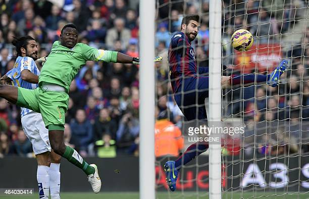 Barcelona's defender Gerard Pique vies with Malaga's Cameroonian goalkeeper Carlos Kameni and Malaga's midfielder Sergi Darder during the Spanish...