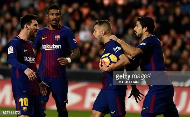 TOPSHOT Barcelona's defender Jordi Alba celebrates after scoring with Barcelona's Uruguayan forward Luis Suarez Barcelona's Brazilian midfielder Jose...