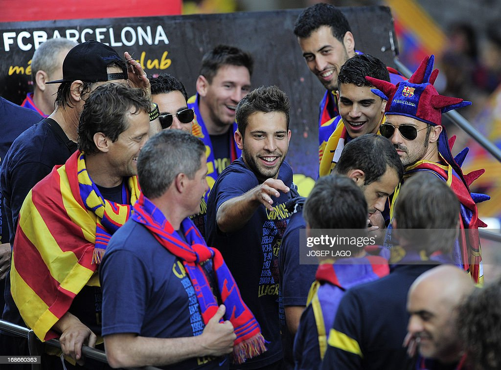 Barcelona's defender Jordi Alba (C) reacts as he and his teammates parade on a bus through a crowd of celebrating supporters in the streets of Barcelona on May 13, 2013, two days after their team won the Spanish league. The Catalans didn't even need to set foot on the pitch to seal the title on May 11 as Real Madrid's 1-1 draw with Espanyol meant Barca had already been crowned champions before their 2-1 win over Atletico Madrid on May 12, 2013. AFP PHOTO/ JOSEP LAGO