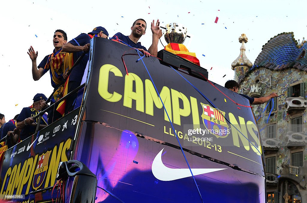 Barcelona's defender Marc Bartra (L) and Barcelona's defender Gerard Pique react as they and their teammates pass by Gaudi's Casa Batllo, on through a crowd of supporters celebrating in the streets of Barcelona on May 13, 2013, two days after their team won the Spanish league. The Catalans didn't even need to set foot on the pitch to seal the title on May 11 as Real Madrid's 1-1 draw with Espanyol meant Barca had already been crowned champions before their 2-1 win over Atletico Madrid on May 12, 2013.