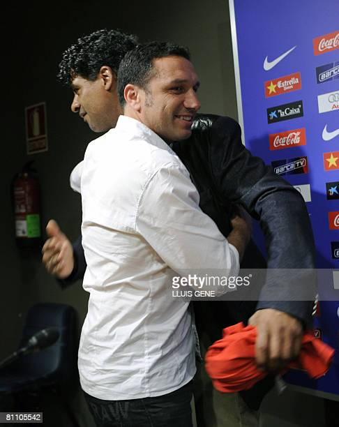 FC Barcelona's Dutch coach Frank Rijkaard says goodbye to his teammate Eusebio Sacristan holding a Tshirt that says in Catalan you 'never smoked...